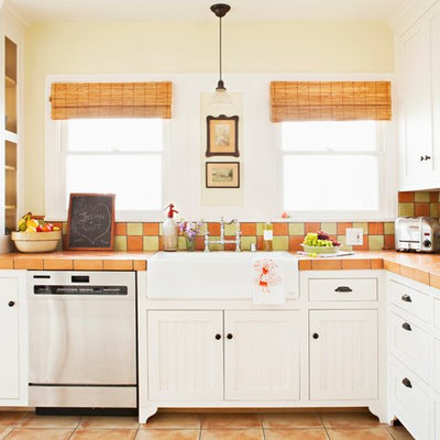 Example of a mid-sized cottage chic l-shaped terra-cotta tile eat-in kitchen design in Los Angeles with beaded inset cabinets, white cabinets, a farmhouse sink, tile countertops, terra-cotta backsplash, stainless steel appliances and multicolored backsplash
