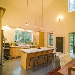 ローリーの小さいカントリー風おしゃれなキッチン (エプロンフロントシンク、フラットパネル扉のキャビネット、淡色木目調キャビネット、コンクリートカウンター、白いキッチンパネル、サブウェイタイルのキッチンパネル、シルバーの調理設備の、コンクリートの床) の写真