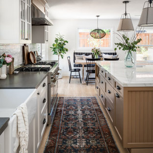 Design ideas for a large beach style l-shaped eat-in kitchen in San Diego with a farmhouse sink, shaker cabinets, light wood cabinets, solid surface benchtops, porcelain splashback, vinyl floors, with island and grey benchtop.