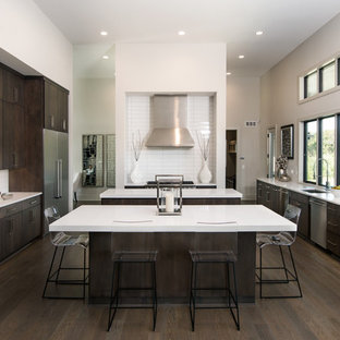 Photo of a large contemporary single-wall open plan kitchen in Wichita with an undermount sink, flat-panel cabinets, dark wood cabinets, white splashback, stainless steel appliances, dark hardwood floors, multiple islands, solid surface benchtops and porcelain splashback.