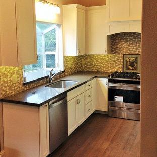 サクラメントの小さいシャビーシック調のおしゃれなキッチン (アンダーカウンターシンク、シェーカースタイル扉のキャビネット、ステンレスキャビネット、クオーツストーンカウンター、マルチカラーのキッチンパネル、モザイクタイルのキッチンパネル、シルバーの調理設備、無垢フローリング、アイランドなし) の写真