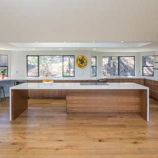 Large trendy u-shaped medium tone wood floor open concept kitchen photo in San Diego with an undermount sink, flat-panel cabinets, dark wood cabinets, quartz countertops, white backsplash, stainless steel appliances and an island