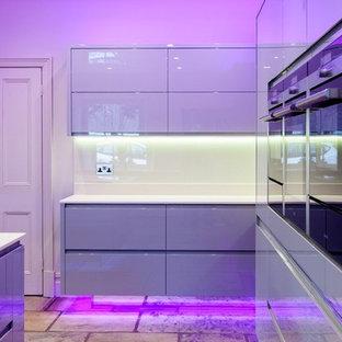 Стильный дизайн: большая параллельная кухня-гостиная в стиле модернизм с накладной раковиной, плоскими фасадами, серыми фасадами, столешницей из ламината, белым фартуком, техникой из нержавеющей стали, кирпичным полом и островом - последний тренд