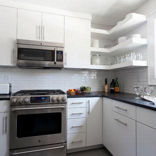 Aménagement d'une petit cuisine moderne en U fermée avec un évier encastré, des portes de placard blanches, une crédence blanche, une crédence en carreau de céramique, un électroménager en acier inoxydable, un sol en linoléum et un îlot central.