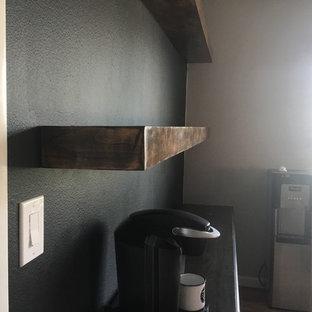 Klassisk inredning av ett litet linjärt kök, med skåp i mörkt trä, bänkskiva i zink, svart stänkskydd, mellanmörkt trägolv, brunt golv och svarta vitvaror