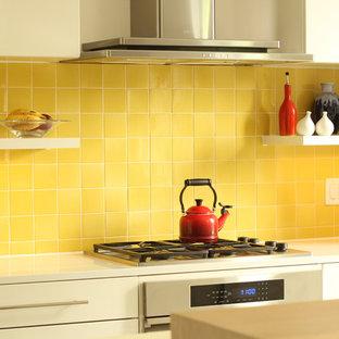 Offene, Einzeilige, Kleine Moderne Küche mit Doppelwaschbecken, flächenbündigen Schrankfronten, weißen Schränken, Quarzwerkstein-Arbeitsplatte, Küchenrückwand in Gelb, Rückwand aus Keramikfliesen, Elektrogeräten mit Frontblende, Betonboden und Kücheninsel in Sonstige