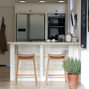 This is an example of a medium sized contemporary enclosed kitchen in Other with shaker cabinets, white cabinets, marble worktops, stainless steel appliances, travertine flooring and a breakfast bar.