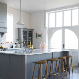 Traditional galley kitchen/diner in Other with a belfast sink, recessed-panel cabinets, grey cabinets, white splashback, an island, grey floors and white worktops.