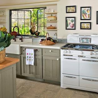 Landhausstil Küche mit Landhausspüle, Schrankfronten mit vertiefter Füllung, weißen Elektrogeräten, Betonboden, Kücheninsel und grauen Schränken in Sonstige