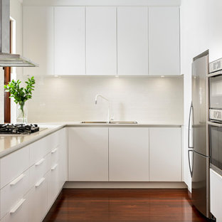 Contemporary u-shaped separate kitchen in Perth with a drop-in sink, flat-panel cabinets, white cabinets, white splashback, subway tile splashback, dark hardwood floors, no island, brown floor and white benchtop.