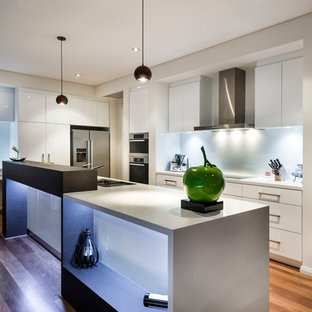 Design ideas for a mid-sized contemporary u-shaped eat-in kitchen in Perth with a double-bowl sink, white cabinets, quartz benchtops, white splashback, glass sheet splashback, stainless steel appliances, medium hardwood floors, with island, brown floor, white benchtop and flat-panel cabinets.