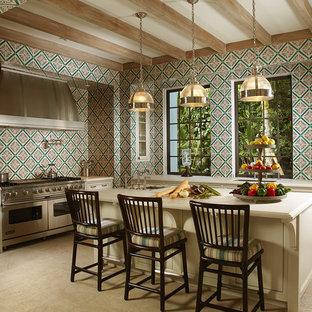 Inredning av ett medelhavsstil kök, med en undermonterad diskho, luckor med infälld panel, beige skåp, flerfärgad stänkskydd och rostfria vitvaror
