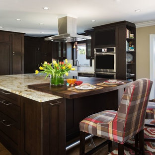Mid-sized transitional l-shaped eat-in kitchen in Miami with a farmhouse sink, shaker cabinets, dark wood cabinets, limestone benchtops, white splashback, ceramic splashback, stainless steel appliances, medium hardwood floors and with island.
