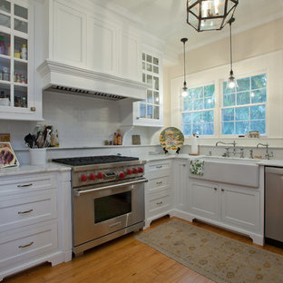 Traditional kitchen designs - Example of a classic kitchen design in Tampa with glass-front cabinets, stainless steel appliances and a farmhouse sink