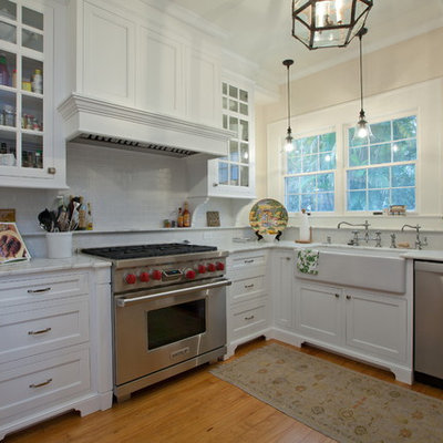 Example of a classic kitchen design in Tampa with glass-front cabinets, stainless steel appliances and a farmhouse sink
