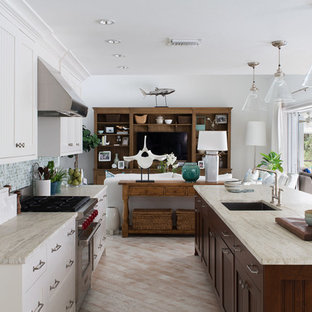 Large coastal galley open plan kitchen in Miami with a submerged sink, marble worktops, multi-coloured splashback, stainless steel appliances, an island, light hardwood flooring, recessed-panel cabinets, white cabinets and mosaic tiled splashback.