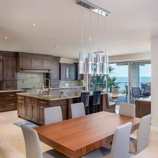 Inredning av ett klassiskt stort beige beige kök, med en undermonterad diskho, luckor med infälld panel, skåp i mörkt trä, granitbänkskiva, beige stänkskydd, stänkskydd i mosaik, rostfria vitvaror, travertin golv, en köksö och beiget golv