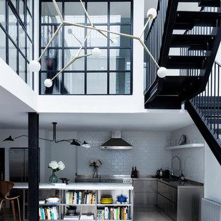 ロンドンの中くらいのインダストリアルスタイルのおしゃれなキッチン (一体型シンク、フラットパネル扉のキャビネット、ステンレスキャビネット、ステンレスカウンター、白いキッチンパネル、セラミックタイルのキッチンパネル、シルバーの調理設備、コンクリートの床) の写真