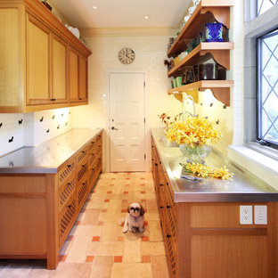 Design ideas for a mid-sized traditional galley kitchen in New York with medium wood cabinets, stainless steel benchtops, white splashback, porcelain splashback, ceramic floors and pink floor.