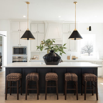 Example of a large transitional l-shaped light wood floor and beige floor open concept kitchen design in Dallas with shaker cabinets, white cabinets, quartzite countertops, white backsplash, stainless steel appliances, an island and white countertops