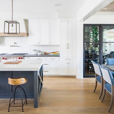 Example of a large cottage galley medium tone wood floor and brown floor open concept kitchen design in Orange County with a farmhouse sink, shaker cabinets, white cabinets, white backsplash, subway tile backsplash, stainless steel appliances, an island and white countertops
