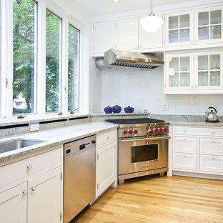 Esempio di una cucina contemporanea con ante di vetro e elettrodomestici in acciaio inossidabile