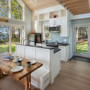 Maritim inredning av ett litet kök med öppen planlösning, med en undermonterad diskho, skåp i shakerstil, vita skåp, granitbänkskiva, blått stänkskydd, stänkskydd i glaskakel, rostfria vitvaror, mellanmörkt trägolv, en köksö och brunt golv