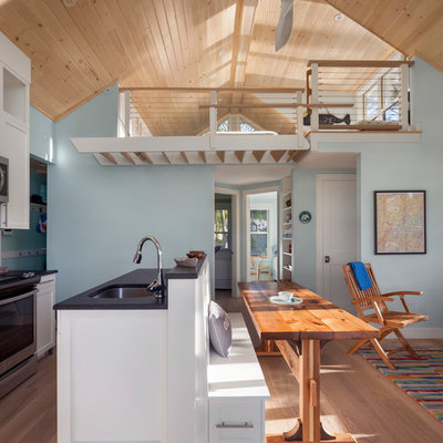 Inspiration for a small coastal medium tone wood floor and brown floor open concept kitchen remodel in Portland Maine with an undermount sink, shaker cabinets, white cabinets, granite countertops, stainless steel appliances and an island