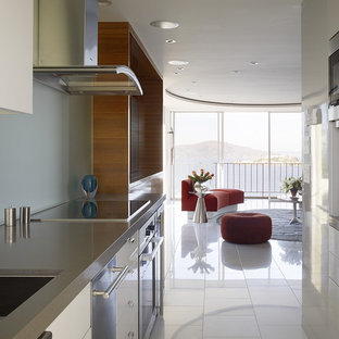 Small modern enclosed kitchen pictures - Small minimalist galley marble floor and white floor enclosed kitchen photo in San Francisco with stainless steel appliances, flat-panel cabinets, white cabinets, quartz countertops, glass sheet backsplash and blue backsplash
