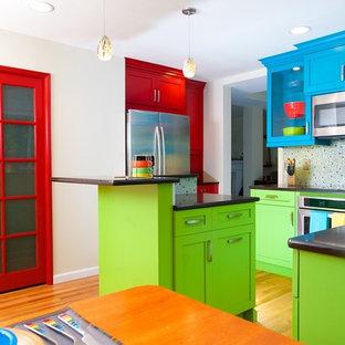 シアトルの中くらいのエクレクティックスタイルのおしゃれなキッチン (アンダーカウンターシンク、落し込みパネル扉のキャビネット、赤いキャビネット、クオーツストーンカウンター、マルチカラーのキッチンパネル、ガラスタイルのキッチンパネル、シルバーの調理設備、無垢フローリング) の写真