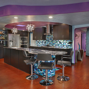 This is an example of a large eclectic l-shaped kitchen in Phoenix with an undermount sink, flat-panel cabinets, granite benchtops, glass tile splashback, stainless steel appliances, medium hardwood floors, with island, brown floor, black cabinets, multi-coloured splashback and grey benchtop.
