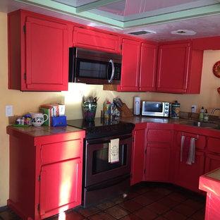 Kleine Moderne Wohnküche in U-Form mit Doppelwaschbecken, Schrankfronten mit vertiefter Füllung, roten Schränken, Arbeitsplatte aus Fliesen, Küchengeräten aus Edelstahl und Terrakottaboden in Phoenix