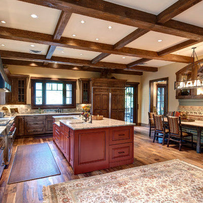 Example of a mountain style l-shaped eat-in kitchen design in Denver with raised-panel cabinets, dark wood cabinets, gray backsplash and paneled appliances