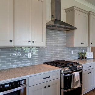 インディアナポリスのラスティックスタイルのおしゃれなキッチン (ドロップインシンク、シェーカースタイル扉のキャビネット、白いキャビネット、御影石カウンター、グレーのキッチンパネル、セラミックタイルのキッチンパネル、シルバーの調理設備の、クッションフロア、茶色い床、ベージュのキッチンカウンター) の写真