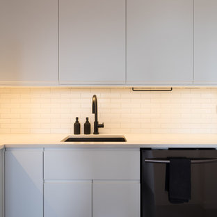 Small contemporary enclosed kitchen designs - Example of a small trendy u-shaped concrete floor and gray floor enclosed kitchen design in New York with an undermount sink, flat-panel cabinets, white cabinets, quartz countertops, white backsplash, subway tile backsplash, black appliances and no island