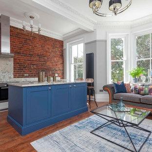 サセックスの小さいエクレクティックスタイルのおしゃれなキッチン (シェーカースタイル扉のキャビネット、青いキャビネット、御影石カウンター、シルバーの調理設備の、無垢フローリング、赤い床、ベージュのキッチンカウンター) の写真