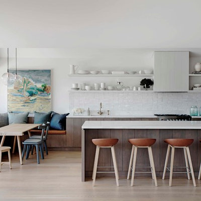 Example of a beach style galley light wood floor eat-in kitchen design in Sydney with white backsplash and a peninsula
