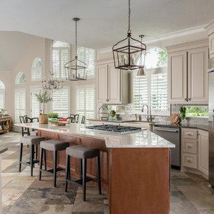 Mittelgroße Klassische Küche in L-Form mit Landhausspüle, profilierten Schrankfronten, beigen Schränken, Küchenrückwand in Grau, Küchengeräten aus Edelstahl, Kücheninsel, Schieferboden, buntem Boden, Quarzit-Arbeitsplatte, Rückwand aus Metrofliesen und brauner Arbeitsplatte in Houston