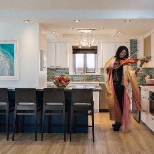 Пример оригинального дизайна интерьера: угловая кухня среднего размера в стиле модернизм с обеденным столом, врезной раковиной, фасадами в стиле шейкер, белыми фасадами, мраморной столешницей, синим фартуком, фартуком из стеклянной плитки, техникой из нержавеющей стали, полом из винила, островом и синей столешницей