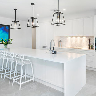 Inspiration for a contemporary galley kitchen in Gold Coast - Tweed with shaker cabinets, white cabinets, grey splashback, stainless steel appliances, with island, grey floor and white benchtop.