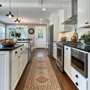 Inspiration for a mid-sized country galley eat-in kitchen in Chicago with a farmhouse sink, shaker cabinets, white cabinets, granite benchtops, white splashback, ceramic splashback, stainless steel appliances, medium hardwood floors, with island, brown floor, black benchtop and coffered.