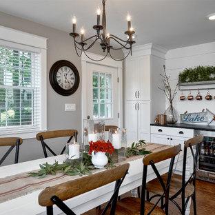 シカゴの中くらいのカントリー風おしゃれなキッチン (エプロンフロントシンク、シェーカースタイル扉のキャビネット、白いキャビネット、御影石カウンター、白いキッチンパネル、シルバーの調理設備、無垢フローリング、茶色い床、黒いキッチンカウンター、塗装板のキッチンパネル) の写真