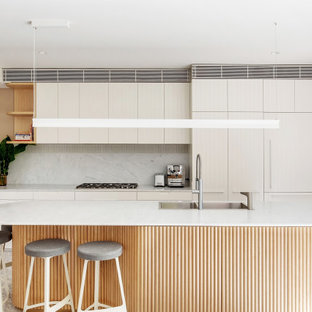 This is an example of a mid-sized contemporary galley eat-in kitchen in Other with a drop-in sink, flat-panel cabinets, white cabinets, white splashback, panelled appliances, terrazzo floors, with island, grey floor and white benchtop.