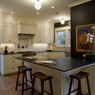 Traditional kitchen remodeling - Example of a classic u-shaped kitchen design in Portland with a farmhouse sink, shaker cabinets, beige cabinets and subway tile backsplash