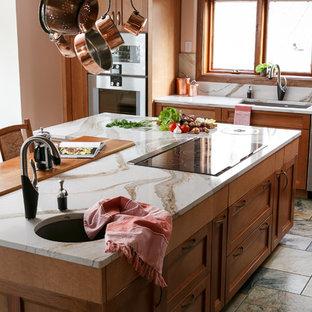 ルイビルの巨大なトランジショナルスタイルのおしゃれなキッチン (アンダーカウンターシンク、落し込みパネル扉のキャビネット、中間色木目調キャビネット、クオーツストーンカウンター、白いキッチンパネル、石スラブのキッチンパネル、シルバーの調理設備、磁器タイルの床、マルチカラーの床、白いキッチンカウンター) の写真