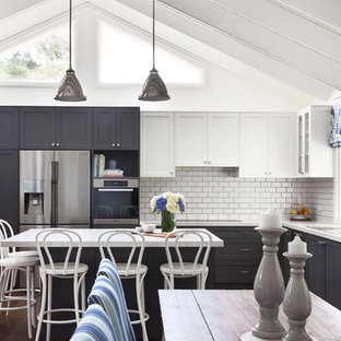 Inspiration for a large beach style l-shaped eat-in kitchen in Sydney with a double-bowl sink, shaker cabinets, black cabinets, white splashback, subway tile splashback, stainless steel appliances, dark hardwood floors, with island and brown floor.
