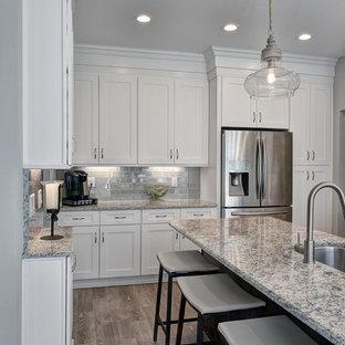 Große Moderne Wohnküche in L-Form mit Unterbauwaschbecken, Schrankfronten im Shaker-Stil, weißen Schränken, Granit-Arbeitsplatte, Küchenrückwand in Grau, Rückwand aus Glasfliesen, Küchengeräten aus Edelstahl, Porzellan-Bodenfliesen, Kücheninsel und braunem Boden in Charleston