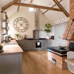 Foto på ett mellanstort lantligt kök, med en rustik diskho, luckor med infälld panel, grå skåp, träbänkskiva, beiget golv, integrerade vitvaror och mellanmörkt trägolv