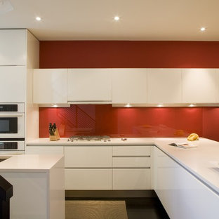 Modern kitchen pictures - Example of a minimalist kitchen design in DC Metro with white appliances, an undermount sink, flat-panel cabinets, white cabinets, red backsplash and glass sheet backsplash
