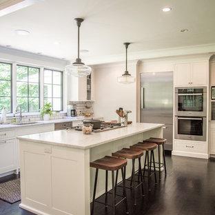 Klassisk inredning av ett avskilt, mellanstort u-kök, med en undermonterad diskho, vita skåp, granitbänkskiva, vitt stänkskydd, stänkskydd i tunnelbanekakel, rostfria vitvaror, mörkt trägolv, en köksö, brunt golv och skåp i shakerstil